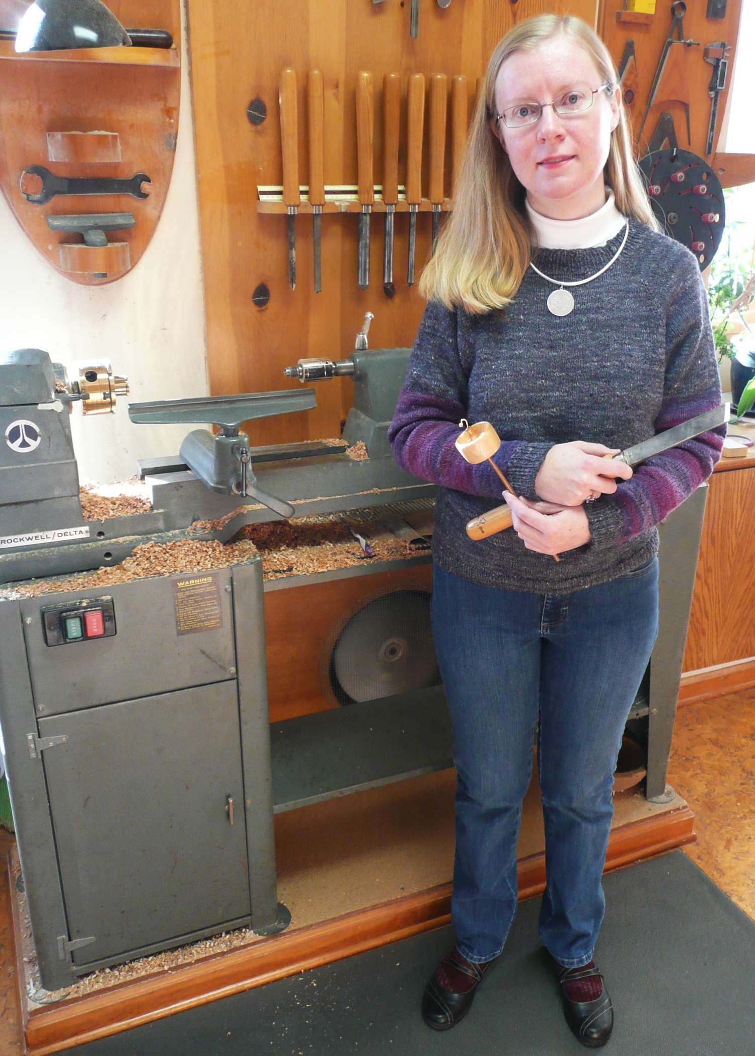 Cynthia D. Haney in front of her lathe holding a top whorl drop spindle that she made with the skew chisel.  Sweater hand knit from yarn entirely spindle spun and plied by her on her own hand turned spindles.