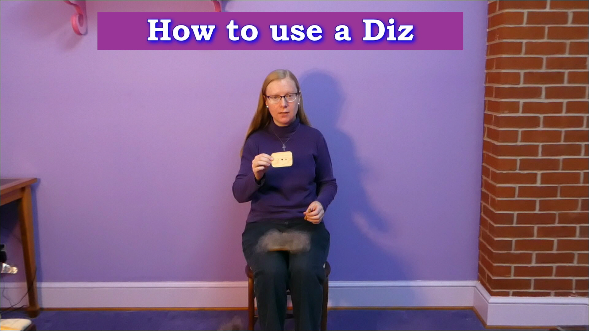 Picture of Cynthia D. Haney seated in a purple room.  Holding a diz, threader, and hand card full of wool.  Links to a video on how to use a diz.