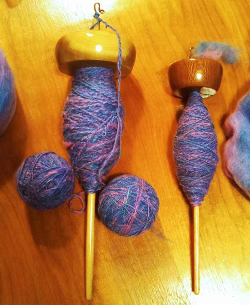 A drop spindle of Tulip Poplar holding two ply yarn being spun from a pair of plying balls.  Also a top whorl drop spindle of Sycamore on Maple with singles being spun.  Fiber from Kid Hollow Farm, spindles and spinning by Cynthia D. Haney.