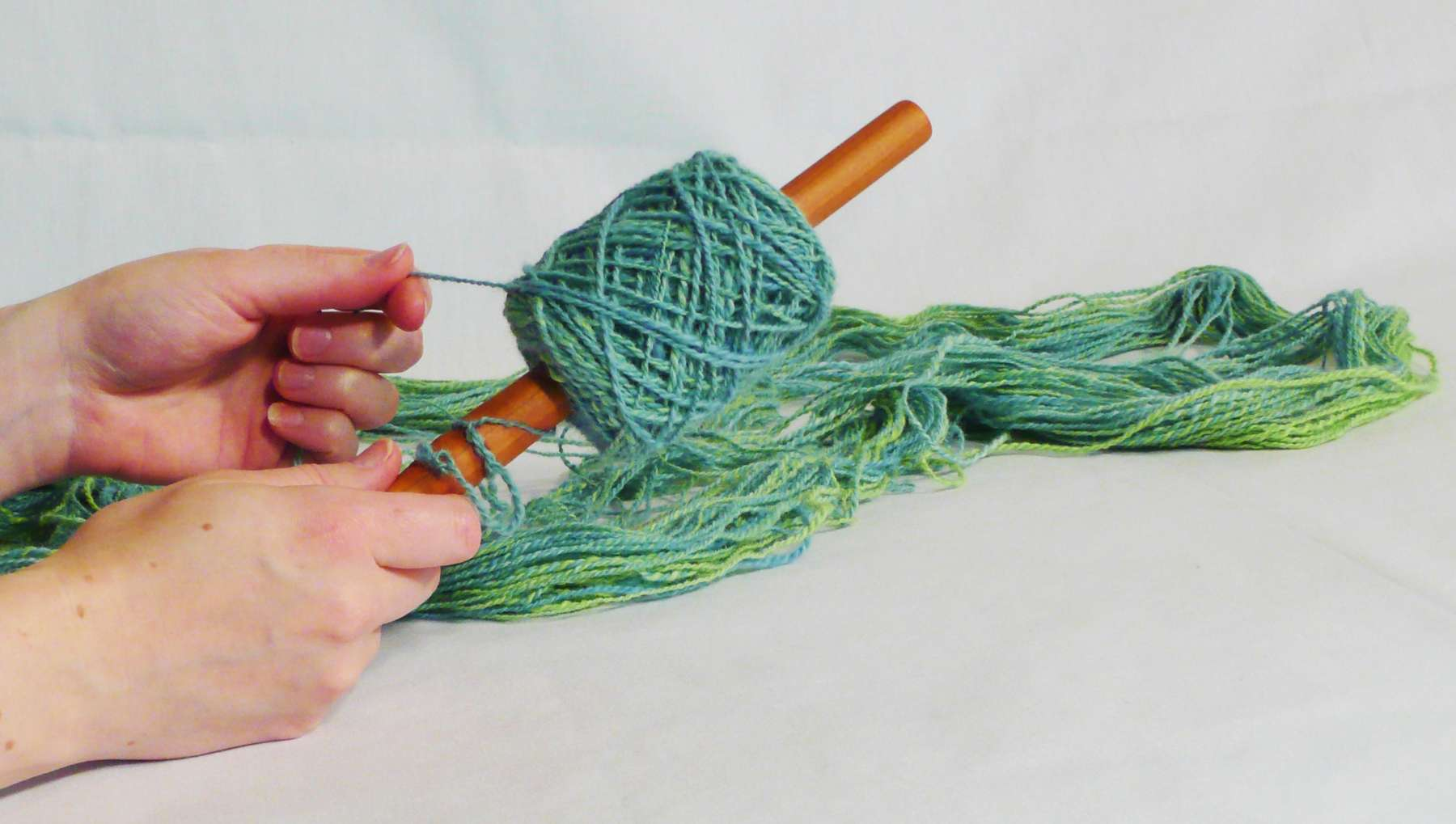 How to use a nostepinne to make a yarn ball, yarn cake, avoid yarn barf.  Pictorial guide using a nostepinne hand made by Cynthia D. Haney