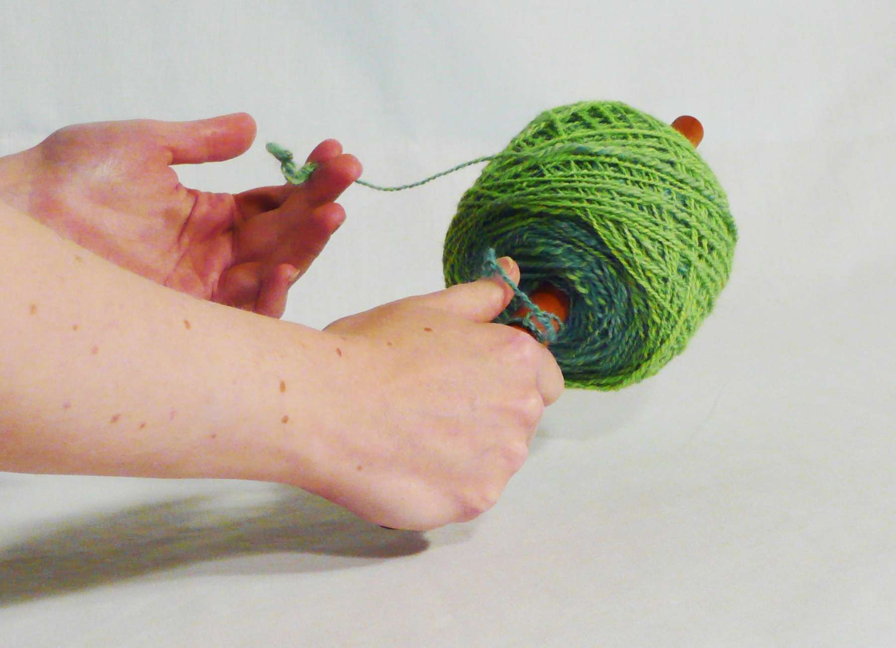 How to use a nostepinne getting from skein to yarn ball, center pull.  Photo tutorial step 12.  On a cherry wood nostepinne hand turned by owner artisan Cynthia D. Haney in her Virginia wood shop.