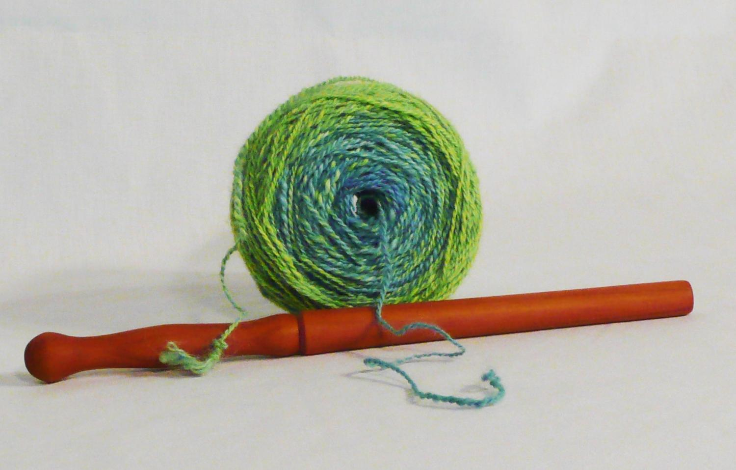 How to use a nostepinne the tool and the result a tangle free center feed yarn ball.  Featuring a cherry wood hand turned ball winding stick hand made by Cynthia D. Haney.