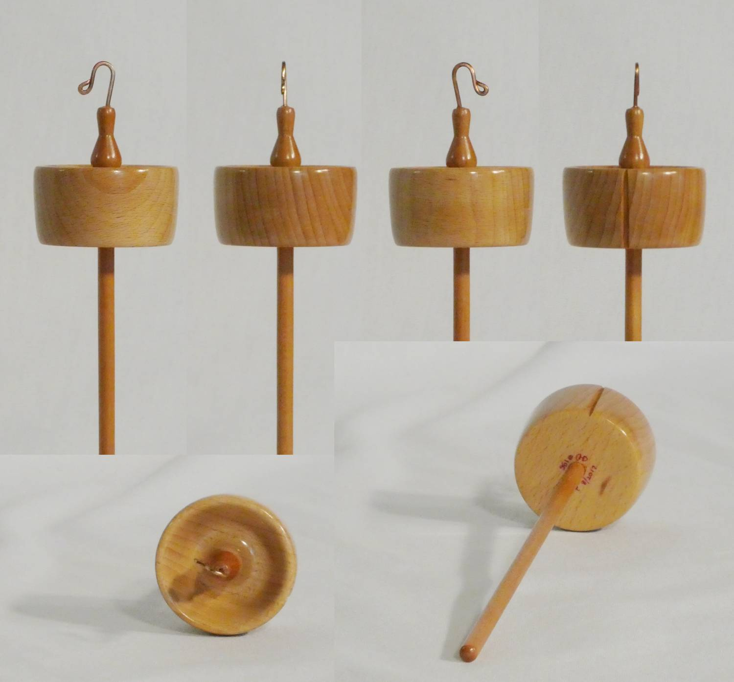 High whorl suspended spindle for spinning yarn from wool handmade by Cynthia D. Haney, a woman woodturner, from Beech and Cherry woods.  Signed number 196.